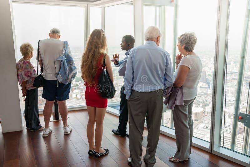 Situación del grupo de personas en un piso superior del edificio alto que habla con perspectiva con la opinión de la ciudad abajo fotos de archivo libres de regalías