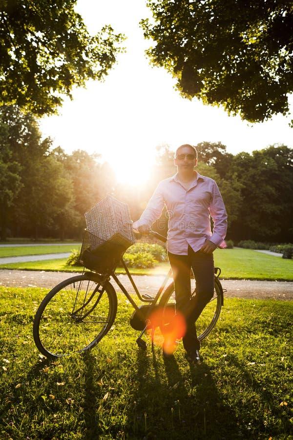 Situación del hombre cerca de la bici con la cesta de la comida campestre en parque fotografía de archivo