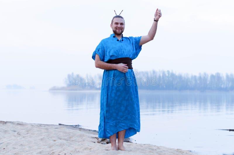 Situación del hombre con la mano extendida, sonriendo y mirando la cámara en la orilla del río arenosa imágenes de archivo libres de regalías