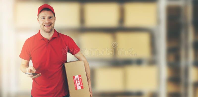 Situación del hombre de entrega en el almacén que sostiene la caja de cartón y el teléfono móvil fotografía de archivo