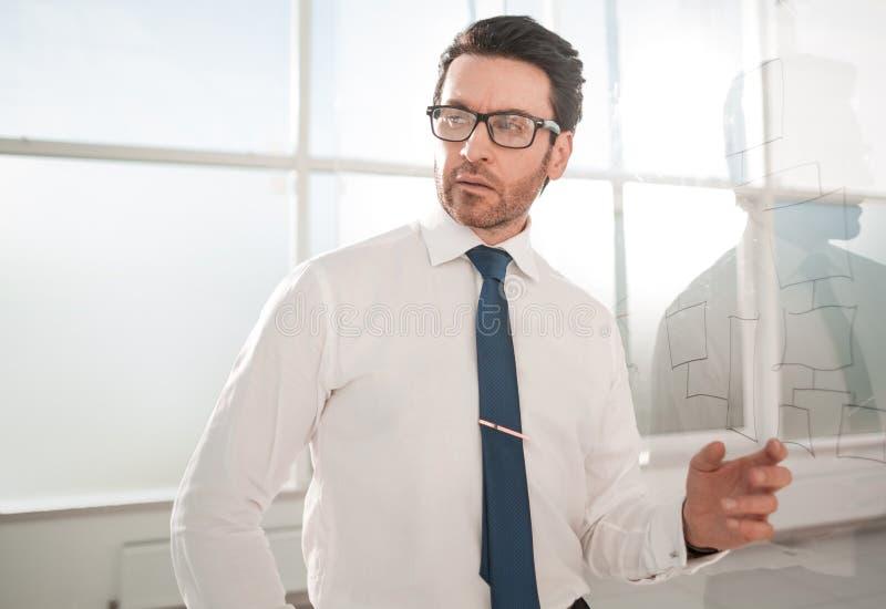 Situación del hombre de negocios cerca de un tablero de cristal foto de archivo