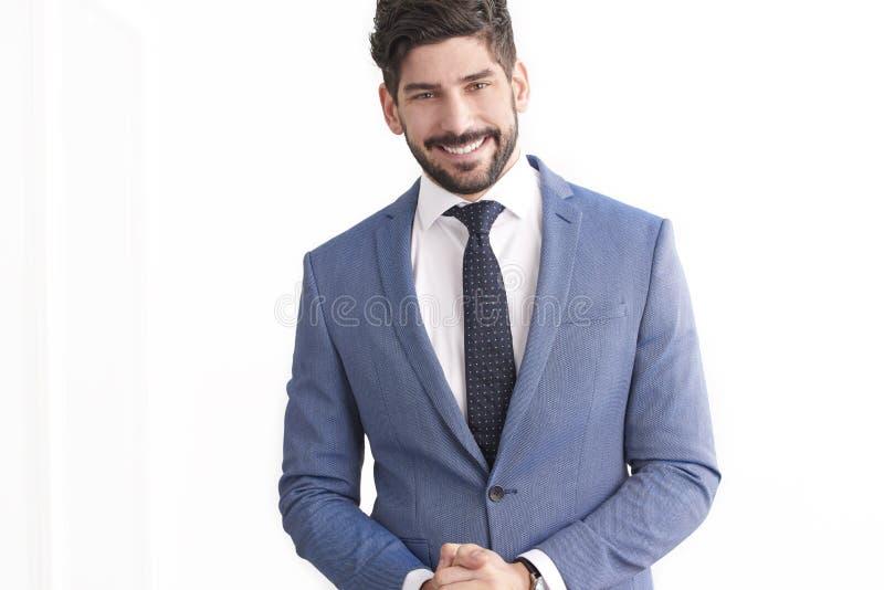 Situación del hombre de negocios en el fondo blanco aislado y el traje que lleva imagenes de archivo