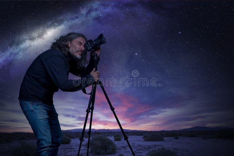 Situación del hombre en la cámara debajo de un cielo estrellado imágenes de archivo libres de regalías