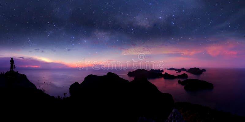 Situación del hombre en la montaña con la opinión del panorama y millón de galaxias de las estrellas fotos de archivo libres de regalías