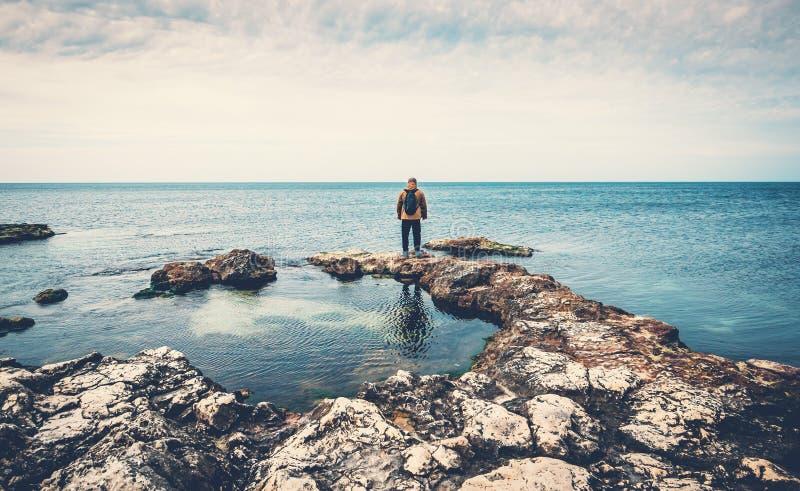 Situación del hombre en piedras en la costa de mar que mira horizonte Playa, viaje del océano y concepto de la libertad imagen de archivo libre de regalías