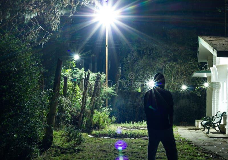 Situación del hombre en un césped que mira las estrellas en el cielo nocturno durante una noche fría del invierno tiro largo de l foto de archivo