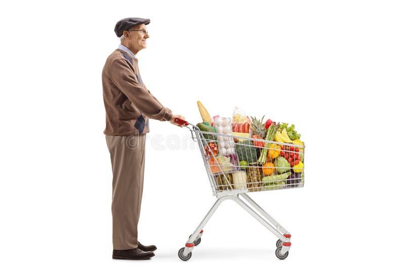 Situación del hombre mayor y el esperar con un carro de la compra con los productos alimenticios imagen de archivo