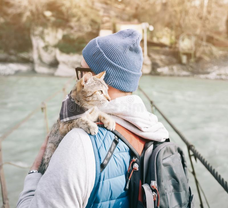 Situación del hombre del viajero en el puente sobre el río con el gato fotos de archivo libres de regalías