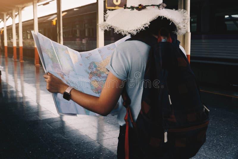 Situación del mapa de la tenencia del viajero de la mujer joven en la plataforma en la estación de tren para el viaje Concepto de imagen de archivo libre de regalías