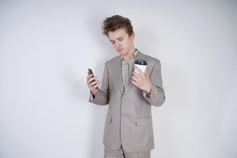 Situación del muchacho del adolescente del estudiante con los ojos cerrados con café y smartphone traje de negocios que lleva del imagenes de archivo