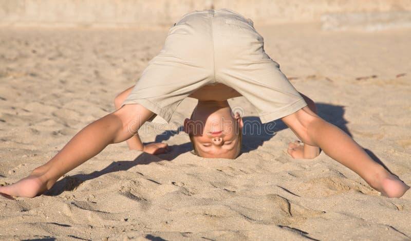 Situación del muchacho en su cabeza en una arena foto de archivo libre de regalías