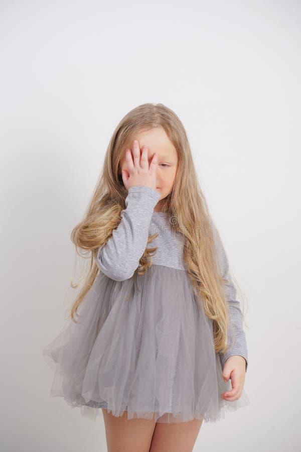 Situación del niño de la niña con una mano en la cara con símbolo del facepalm en el fondo blanco en estudio imagen de archivo