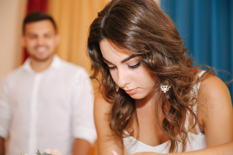 Situación del novio y de la novia dentro de la casa del matrimonio y firmar el papel Pares hermosos en blanco foto de archivo libre de regalías