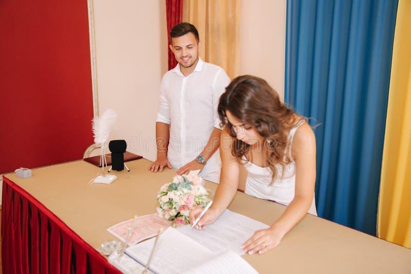 Situación del novio y de la novia dentro de la casa del matrimonio y firmar el papel Pares hermosos en blanco foto de archivo