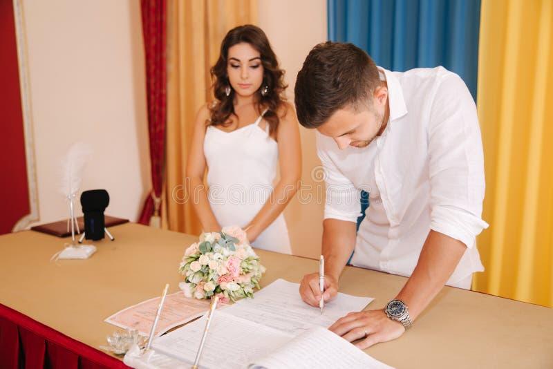 Situación del novio y de la novia dentro de la casa del matrimonio y firmar el papel Pares hermosos en blanco imagen de archivo