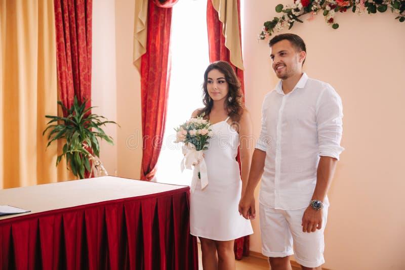 Situación del novio y de la novia dentro de la casa del matrimonio Pares hermosos en blanco fotos de archivo