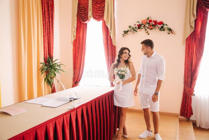Situación del novio y de la novia dentro de la casa del matrimonio Pares hermosos en blanco foto de archivo libre de regalías