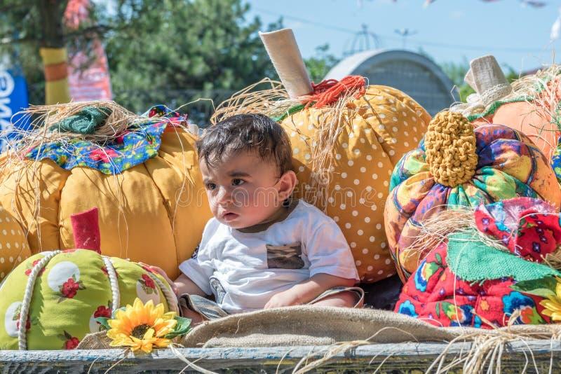 situación del pequeño niño y el parecer de la esquina en un coche de caballo de madera foto de archivo