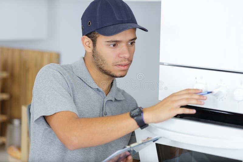 Situación del trabajador joven del retrato en cocina foto de archivo