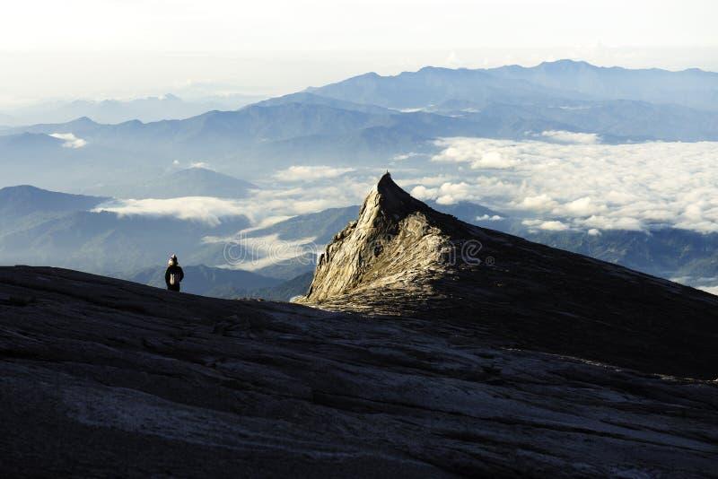 Situaci?n del Trekker en la monta?a de Kinabalu con el pico del sur y cordillera en fondo imagen de archivo libre de regalías