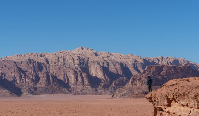Situación del viajero en el borde del acantilado de la montaña, en el desierto de Wadi Rum en Jordania Forma de vida del viaje y  imagen de archivo