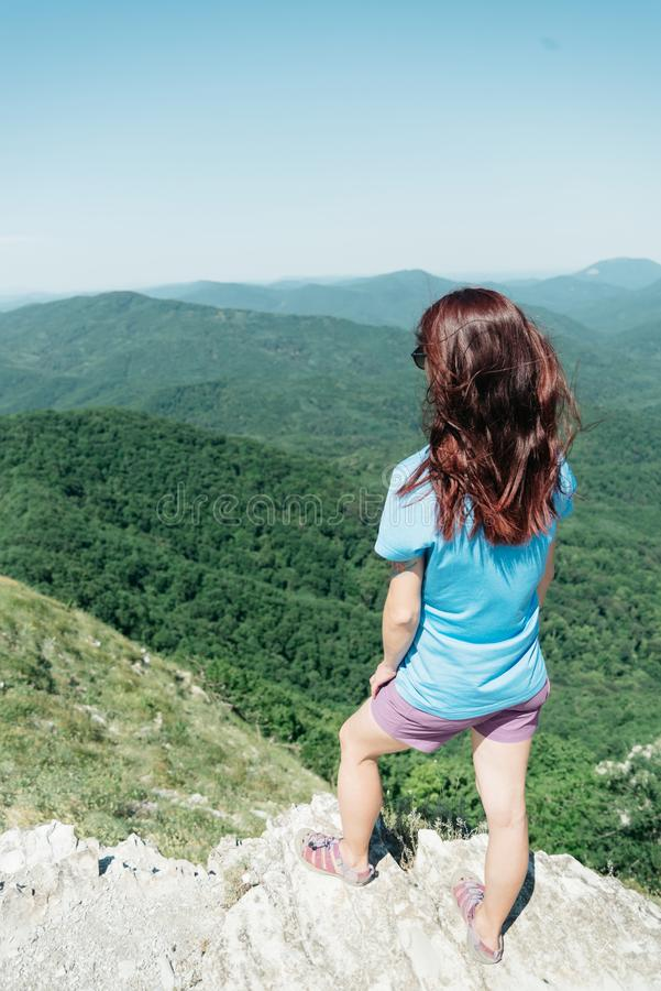 Situación deportiva de la mujer en el pico del acantilado en verano imagen de archivo libre de regalías