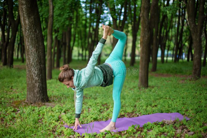 Situación deportiva hermosa fina de la muchacha en la actitud de la media luna, ejercicio de Ardha Chandrasana en un parque del v imagenes de archivo