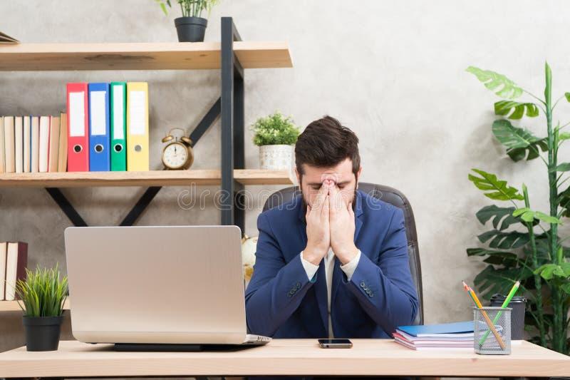 Situación desesperada El jefe barbudo del hombre sienta la oficina con el ordenador portátil Encargado que soluciona problemas de fotos de archivo libres de regalías