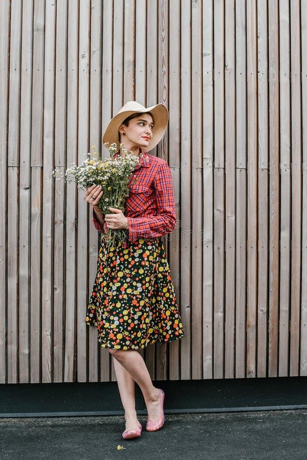 Situación elegante de la muchacha con las flores Mujer hermosa cerca de una pared de madera Estilo de la primavera Paseo del vera imagen de archivo