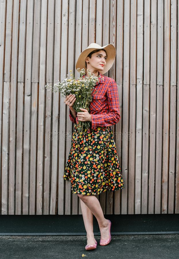 Situación elegante de la muchacha con las flores Mujer hermosa cerca de una pared de madera Estilo de la primavera Paseo del vera imagen de archivo libre de regalías