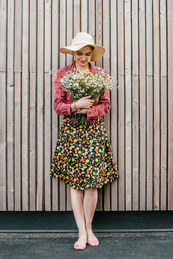Situación elegante de la muchacha con las flores Mujer hermosa cerca de una pared de madera Estilo de la primavera Paseo del vera fotografía de archivo