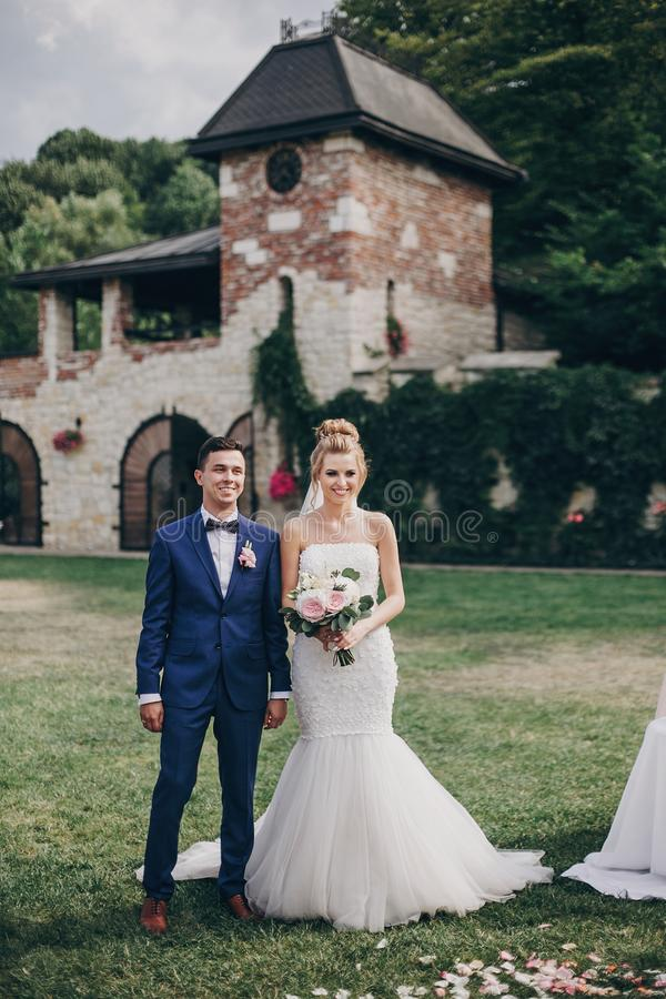 Situación elegante hermosa de novia y del novio en casarse el pasillo con los pétalos color de rosa en hierba durante matrimonio, foto de archivo
