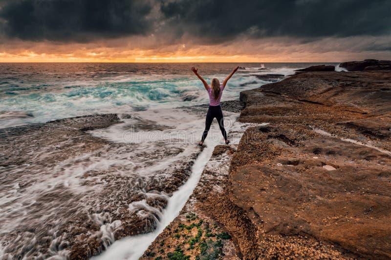Situación enérgica de la muchacha sobre la grieta de la roca como las ondas se lavan adentro fotografía de archivo libre de regalías