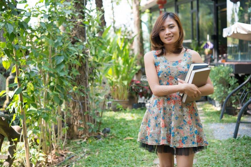 Situación encantadora feliz de la mujer joven y cuadernos el sostenerse en el hom fotos de archivo