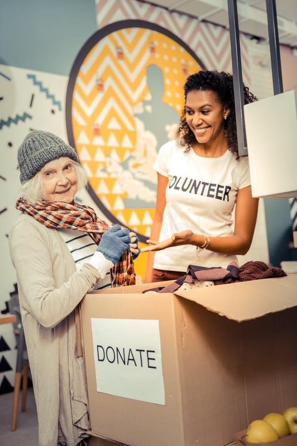 Situación envejecida alegre de la mujer cerca de la caja de la donación foto de archivo libre de regalías