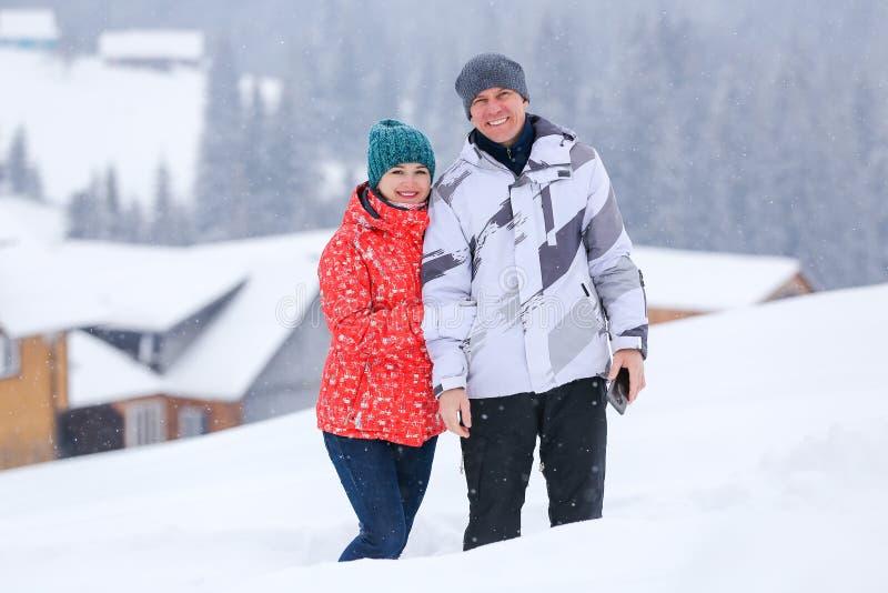 Situación feliz de los pares en la colina nevosa en invierno fotografía de archivo