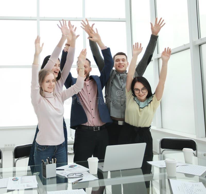 Situación feliz del equipo del negocio cerca de la mesa con las manos para arriba imagenes de archivo