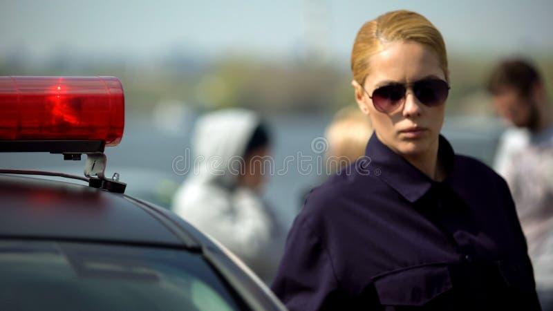 Situación femenina concentrada cerca del coche policía, accidente del oficial en fondo fotografía de archivo libre de regalías