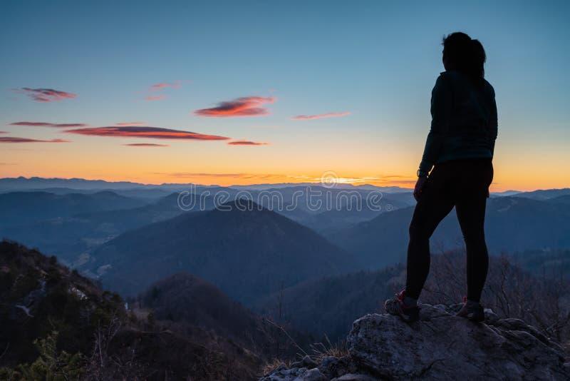 Situación femenina del caminante encima de la colina y disfrutar de la visión después de la puesta del sol imágenes de archivo libres de regalías