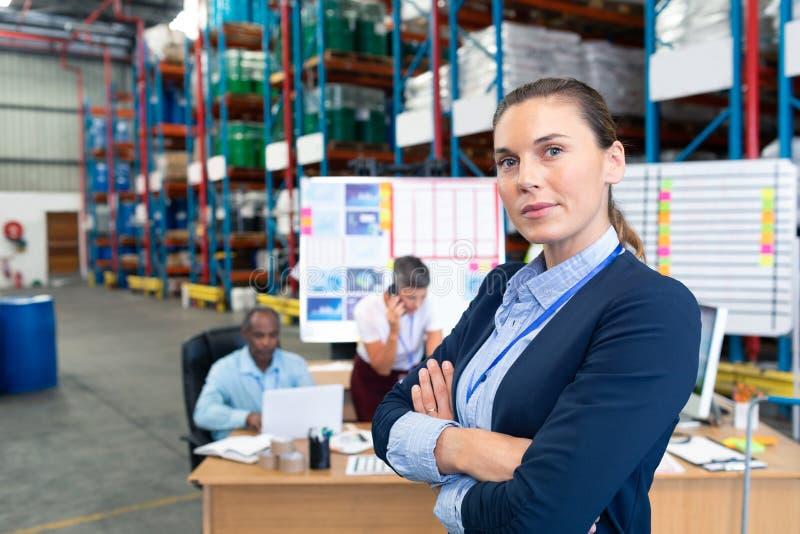 Situación femenina del encargado con los brazos cruzados en almacén fotografía de archivo libre de regalías