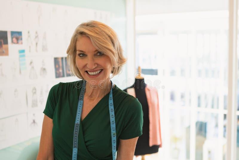 Situación femenina feliz del diseñador de moda en estudio del diseño imagen de archivo libre de regalías