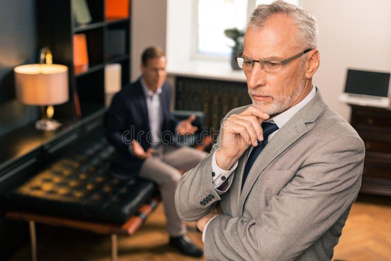 Situación gris-cabelluda pensativa seria del psicoanalista en su oficina fotografía de archivo libre de regalías