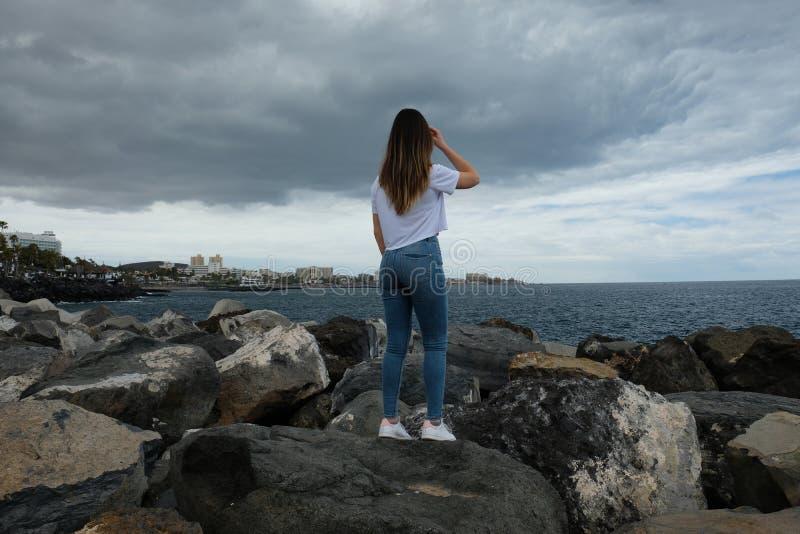 Situación hermosa de la muchacha en las rocas de la playa que miran al mar fotografía de archivo