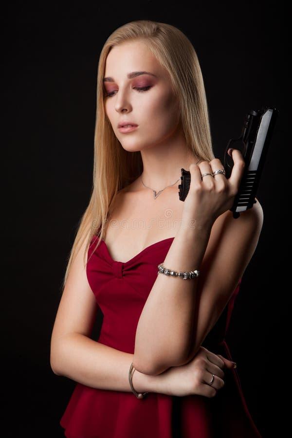 Situación hermosa de la mujer del gángster con el arma en un negro foto de archivo