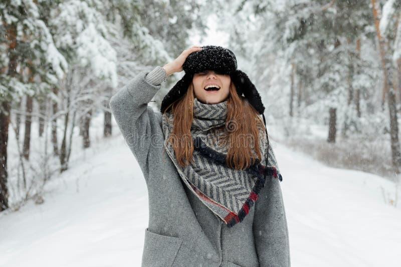 Situación hermosa de la mujer joven entre árboles nevosos en bosque del invierno y nieve del goce fotografía de archivo libre de regalías
