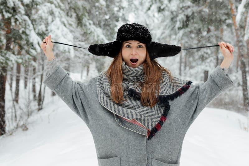 Situación hermosa de la mujer joven entre árboles nevosos en bosque del invierno y nieve del goce fotos de archivo libres de regalías