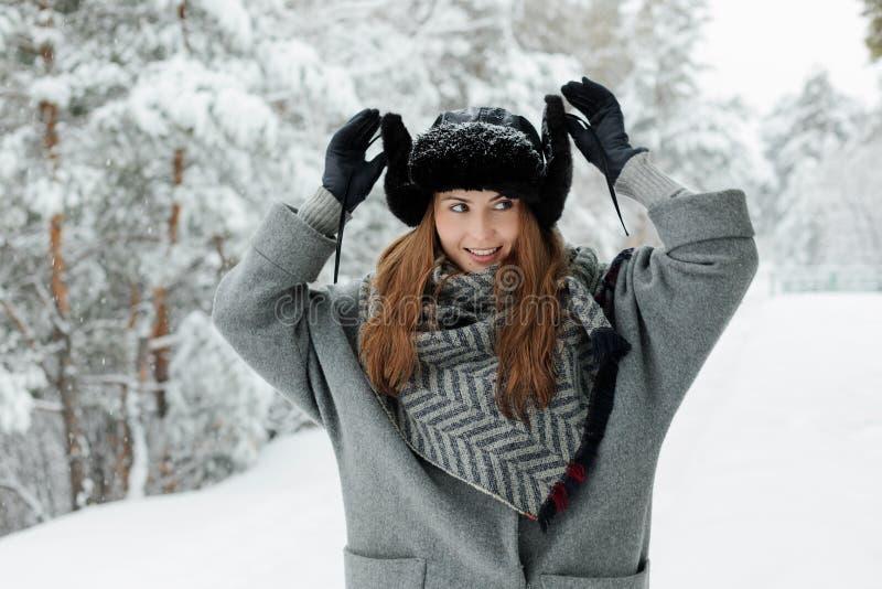 Situación hermosa de la mujer joven entre árboles nevosos en bosque del invierno y nieve del goce imagenes de archivo