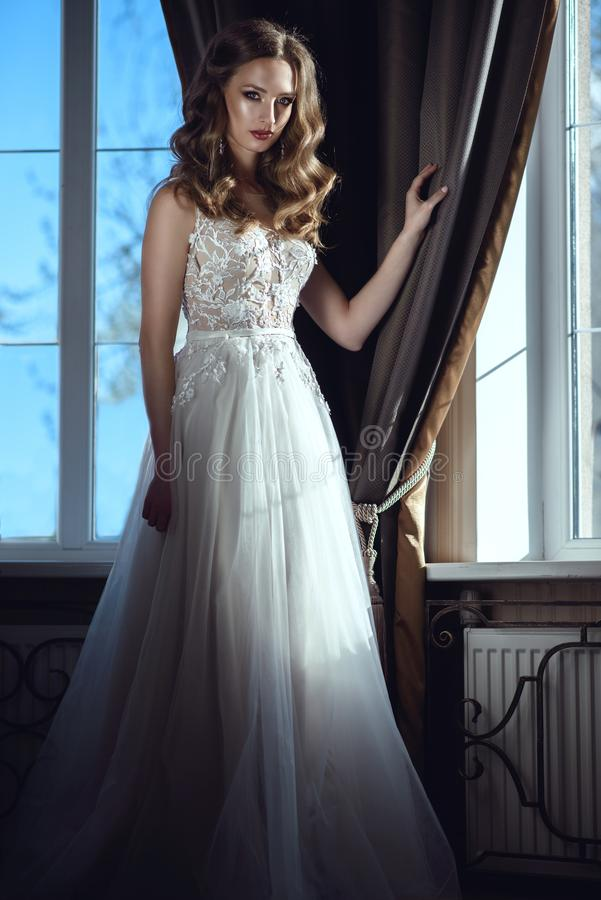 Situación hermosa de la novia en la ventana grande con las cortinas en vestido que se casa lujoso imagen de archivo