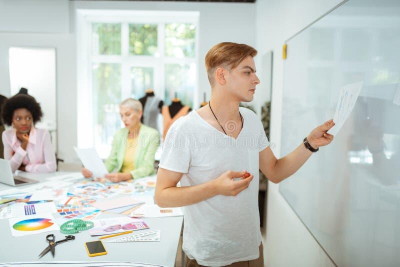 Situación hermosa del hombre ocupado delante del whiteboard foto de archivo libre de regalías