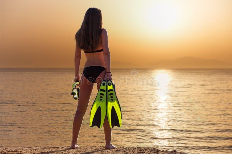Situación hermosa joven de la muchacha con el tubo respirador y las aletas cerca del mar fotografía de archivo libre de regalías